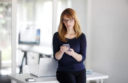 Portrait of confident sales woman using her mobile phone while standing at office desk.